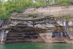 在一个湖岸洞的五颜六色的岩石 免版税库存照片
