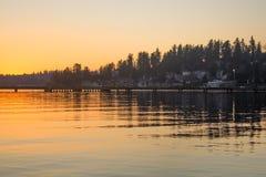 在一个湖的一个码头在Juanita海湾公园,柯克兰,华盛顿的冬天日落的 免版税库存图片