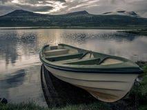 在一个湖的偏僻的渔夫小船在Rondane Nationa的日落的 图库摄影