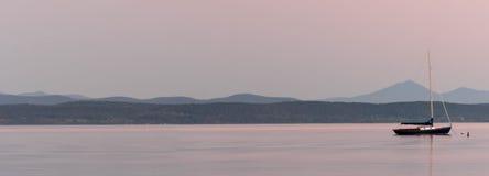 在一个湖的停住的风船有山的在背景中在日落 库存图片