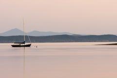在一个湖的停住的风船有山的在背景中在日落 免版税库存照片