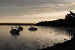 在一个湖的小船日出的 图库摄影