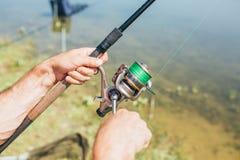 在一个湖的年轻人渔从在日落的小船 库存图片