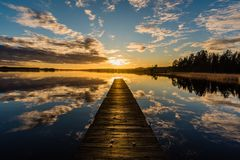 在一个湖的日落在Nykroppa,菲利普斯塔德,有跳船的瑞典 免版税库存照片