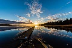 在一个湖的日落在Nykroppa,菲利普斯塔德,有跳船的瑞典 免版税图库摄影