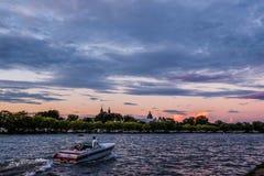 在一个湖的汽艇乘驾日落的 库存照片