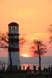 在一个湖的灯塔日落的 库存照片