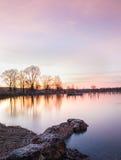 在一个湖的石头在日落期间 库存图片
