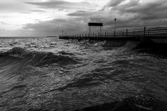 在一个湖的码头有多暴风雨的天气和大波浪的 库存图片