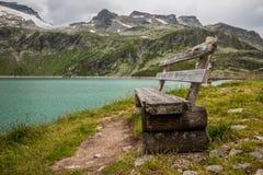 在一个湖的老长木凳在阿尔卑斯 免版税库存照片