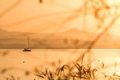 在一个湖的金黄日落有一条小的小船的 免版税库存图片