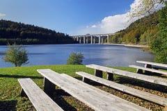 在一个湖的长凳以高速公路桥梁为目的 库存图片