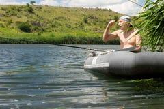 在一个湖的年长渔夫渔从充气救生艇 免版税库存照片