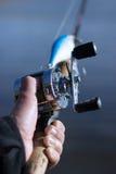 在一个湿圆的渔卷轴的男性手 库存图片