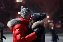 在一个滑冰的溜冰场中间的年轻爱恋的夫妇立场在夜和亲吻里 天圣徒Vadentin,冬天 免版税库存照片