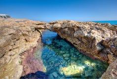 在一个潮汐水池的自然岩石曲拱在海边 免版税图库摄影