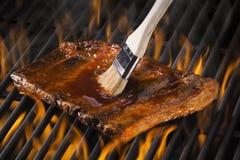 在一个火焰状热的格栅的烤肋骨 库存图片