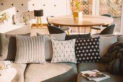 在一个灰色沙发的黑白装饰枕头在被日光照射了锂 免版税库存照片