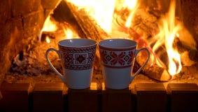 在一个灼烧的壁炉的背景的两个茶杯 库存照片