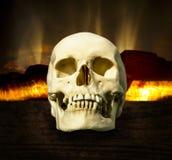 在一个灼烧的壁炉的背景的头骨 免版税库存照片