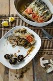 在一个烘烤的盘的被烘烤的河鱼用香料和菜在木背景 适当的营养 顶视图 图库摄影