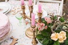 在一个烛台的桃红色蜡烛在桌上 免版税库存照片