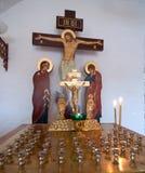 在一个烛台的蜡烛在耶稣受难象前 库存照片