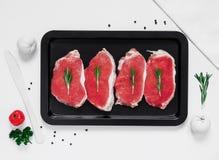 在一个烤板的未加工的新鲜的猪肉牛排在白色背景 免版税库存照片