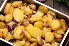 在一个烧烤平底锅的被烘烤的土豆用大蒜 库存图片
