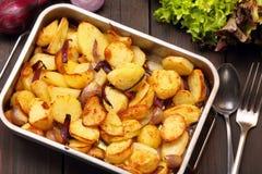 在一个烧烤平底锅的被烘烤的土豆用大蒜 库存照片