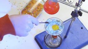 在一个烧瓶的化学家混合蓝色油煎的鸡蛋在实验室,化工实验 股票录像