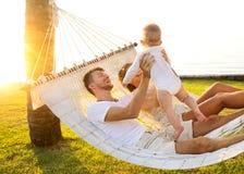 在一个热带海岛上的幸福家庭在吊床的日落谎言的和使用与他们的儿子 库存图片