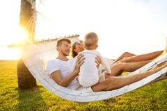 在一个热带海岛上的幸福家庭在吊床的日落谎言的和使用与他们的儿子 免版税库存图片