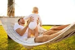 在一个热带海岛上的幸福家庭在吊床的日落谎言的和使用与他们的儿子 免版税库存照片