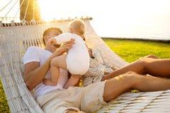 在一个热带海岛上的幸福家庭在吊床的日落谎言的和使用与他们的儿子 图库摄影