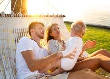 在一个热带海岛上的幸福家庭在吊床的日落谎言的和使用与他们的儿子 库存照片