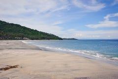 在一个热带海岛上的美妙的看法是与白色沙子的一个离开的海滩,海洋在蓝天下 免版税图库摄影