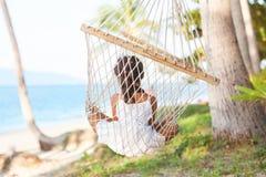 在一个热带海滩的岸的一个吊床的愉快的女孩 免版税库存图片