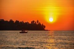 在一个热带海滩的美好的日落 在最后光芒的船风帆 免版税库存照片