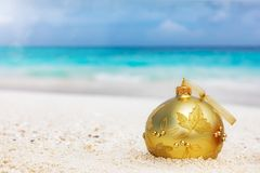 在一个热带海滩的金黄圣诞树球 免版税库存图片