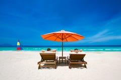 在一个热带海滩的夫妇在轻便折叠躺椅在一把红色伞下 免版税库存照片