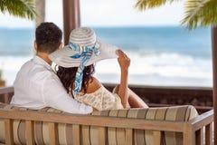 在一个热带海滩的夫妇在轻便马车休息室 库存照片