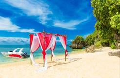 在一个热带海滩的婚礼在红色 用花装饰的曲拱 库存照片