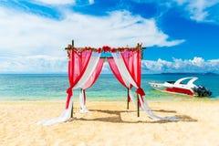 在一个热带海滩的婚礼在红色 用花装饰的曲拱 免版税库存图片