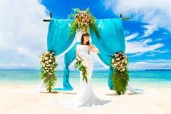 在一个热带海滩的婚礼 在婚礼曲拱下的愉快的新娘 免版税图库摄影