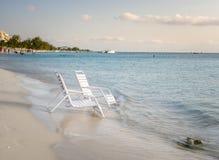在一个热带海滩的岸的白色椅子 免版税图库摄影