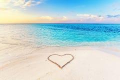 在一个热带海滩的沙子画的心脏在日落 库存图片