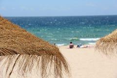 在一个热带海滩的秸杆伞 免版税图库摄影