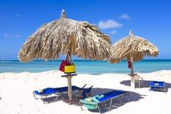 在一个热带海滩的秸杆伞 免版税库存图片