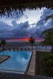 在一个热带海滩的红色日落在游泳池手段 库存照片